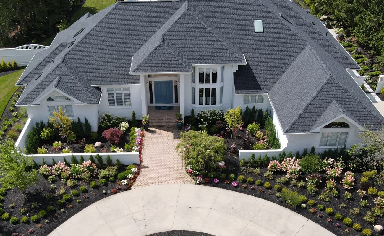 Skyview of Home with Flowerbeds and Trees Lining a Driveway
